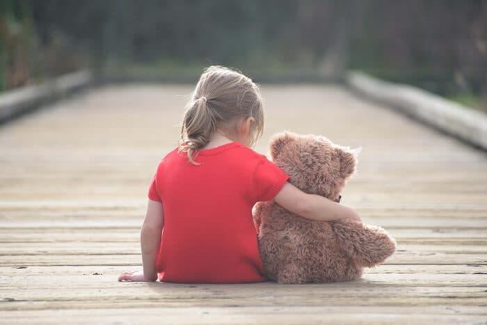 くまのぬいぐるみを抱きしめる女の子